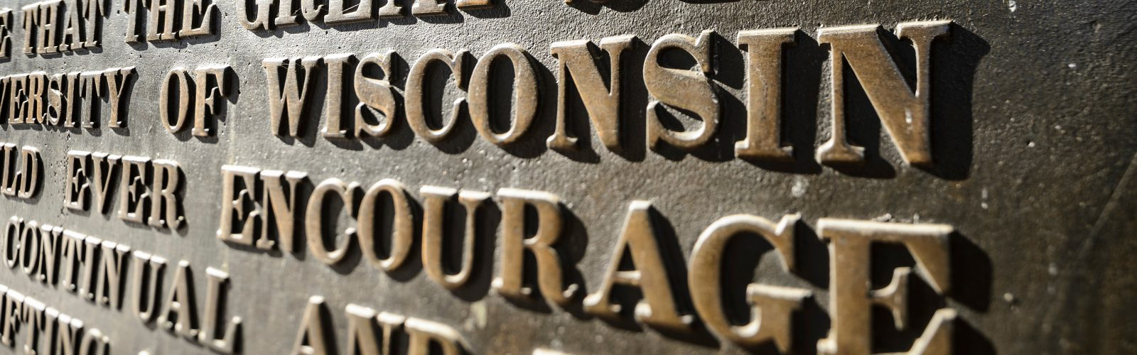 """On Jan. 16, 2018, the winter-morning sunlight shines upon a close-up view of the letters on the """"Sifting and Winnowing"""" plaque, mounted in the arched-portico of Bascom Hall at the University of Wisconsin-Madison. The photograph was made using a tilt/shift-focus lens. (Photo by Jeff Miller / UW-Madison)"""